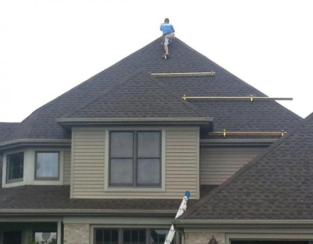 man finishing up new grey architectural shingle roof on house