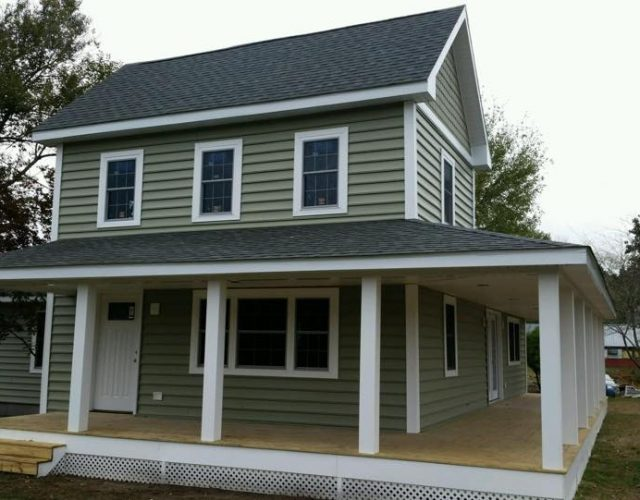 two story home with green caroline beaded siding