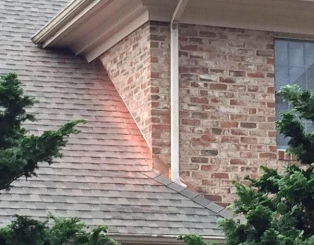 close up of new asphalt shingle roof on brick home