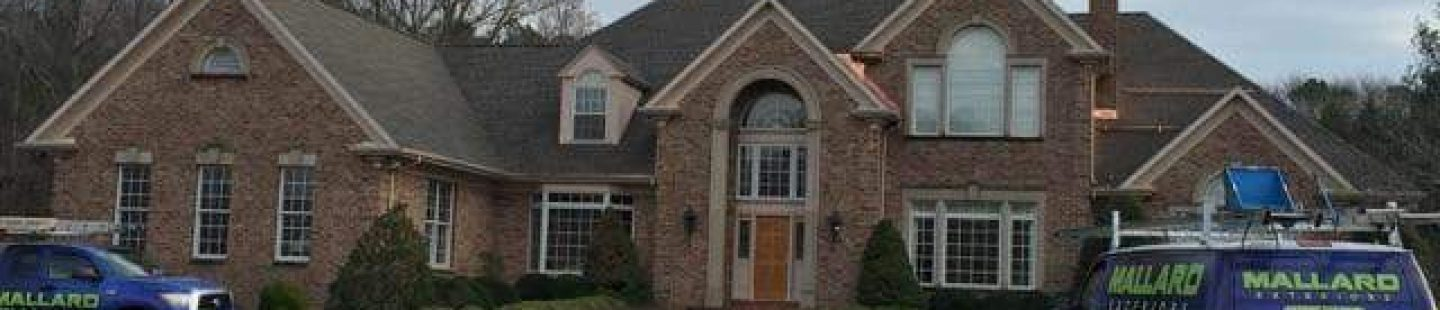 large brick home with new shingle roof