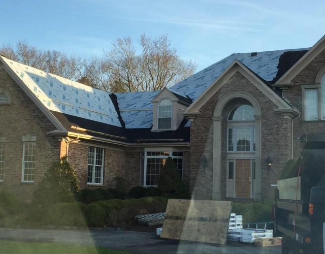 large brick home during original shingle roof removal