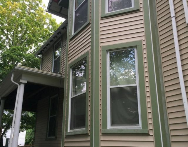 side view of large windows with tan certainteed vinyl siding around them