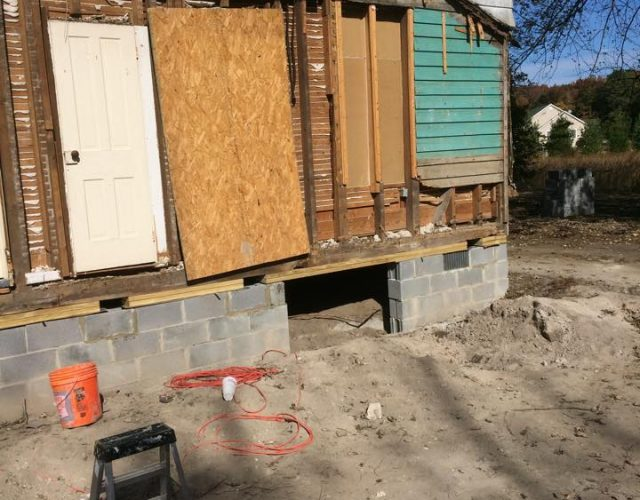 house in the process of vinyl siding removal