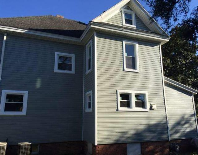 large house with completed gray vinyl siding