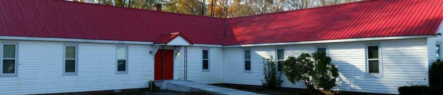 old church with updated red ribbed metal roof