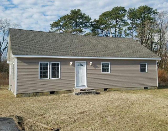 mobile home with new tan vinyl siding and gray shingle roof