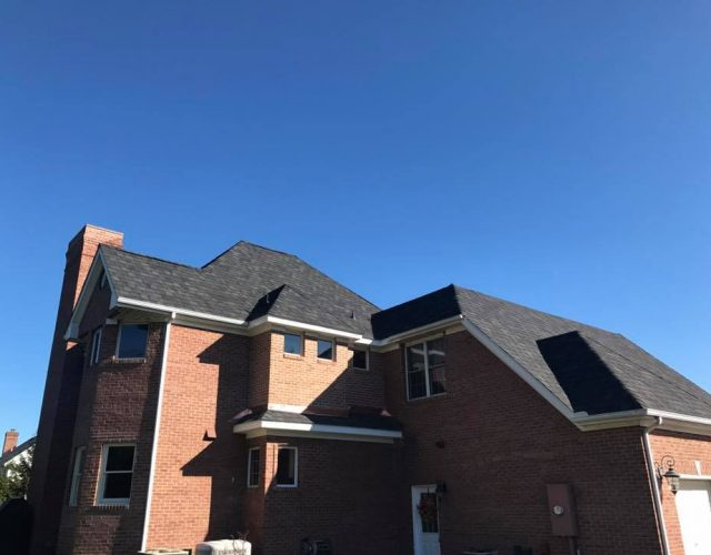 large brick house with completed asphalt roofing