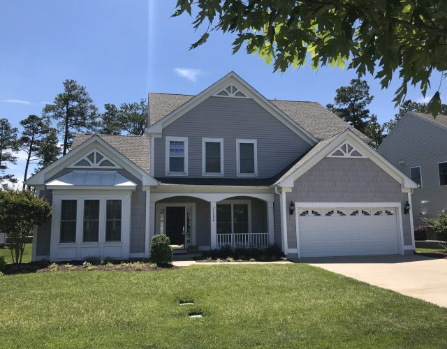 large two story home with gray vinyl siding and asphalt roof