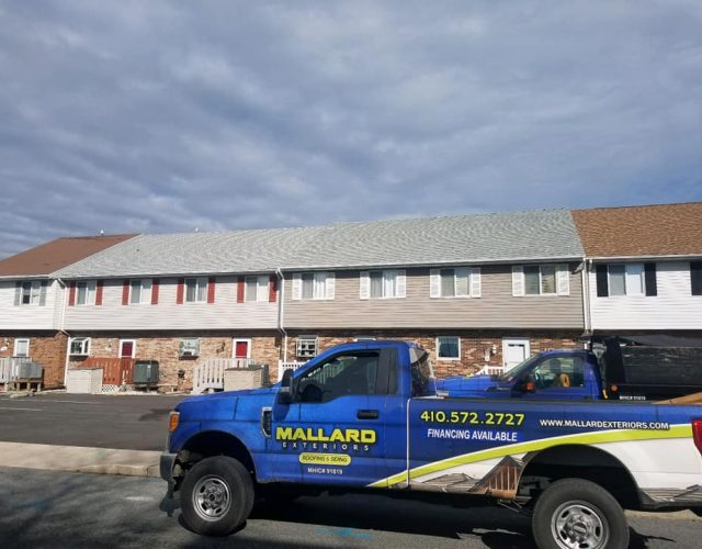 finished roofing project on apartment complexes with mallard truck out front
