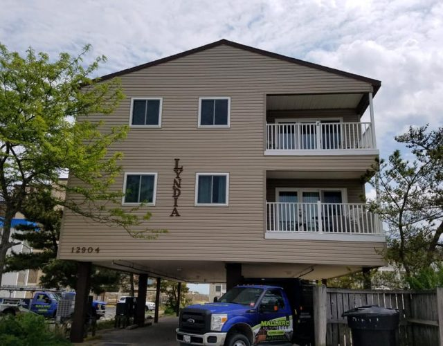 large beach condo with tan vinyl siding and four replaced windows